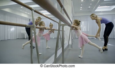 Two girls are practice near barre with coach in ballet...