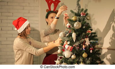Two girls are preparing for Christmas and decorate the Christmas tree