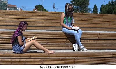 Two girls are reading a book sitting on a wooden bench in the park in sunny weather. slow motion