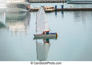 Two girls are sailing on a small sailing boat.