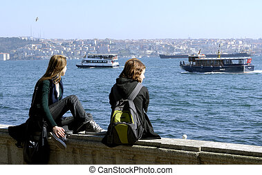 Two girls are sitting  at the Bosporus in Istanbul and are looking from Europe to Asia