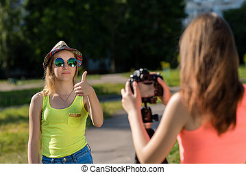 Two girls are students. In summer in city. Dressed in bright clothes. Photographed in nature. Record vlog and blog. Record video lesson for Internet. Use camera with tripod.