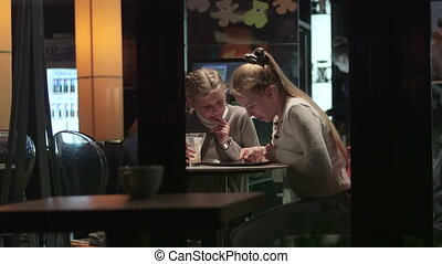 Two girls at city coffee shop through the window