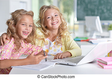 Two girls at class using laptop and writing - two beautiful...