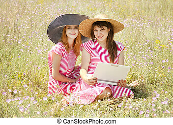 Two girls at contryside with notebook.