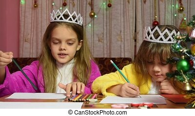 Two girls at the table draw, funny one selects the desired color pencil