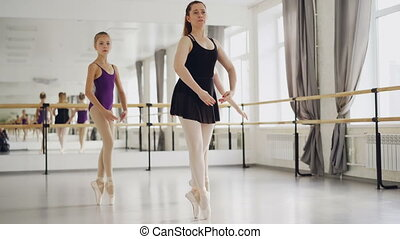 Two girls ballet dancers are practising dancing on tiptoes...