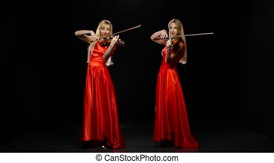Two girls blonde playing the fiddle. Studio. Black...