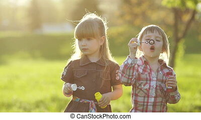 Two girls blowing bubbles - 1