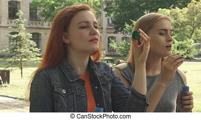 Two girls blowing bubbles outdoors
