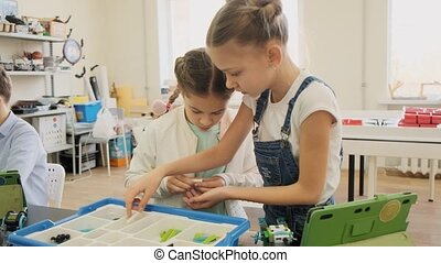 Two girls build the plastic robot using the instruction from...