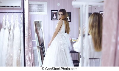 two girls choose a dress in the wedding store - girl chooses...