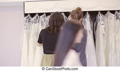 two girls choose dress at bridal boutique