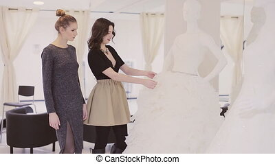 two girls choose dress - two young woman chooses wedding...