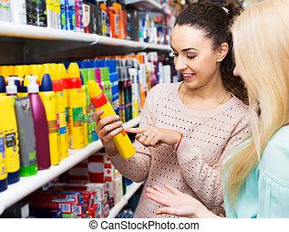 Two girls choosing hair spray - Cheerful brunette offering ...