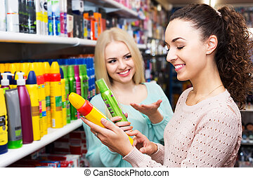 Two girls choosing hair spray - Happy brunette offering ...