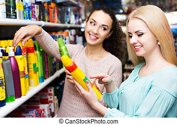 Two girls choosing hair spray - Young cheerful brunette ...
