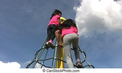 Two Girls Climb A Spinning Carousel - Two cute Asian girls...