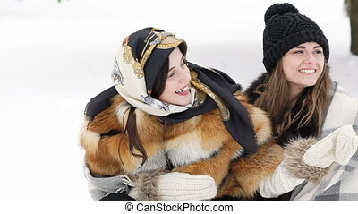 Two girls covered in plaid embracing and smiling in the winter park. Slowly