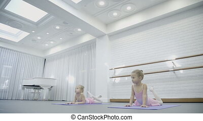 Two girls do arch laying on the mats while ballet class with...