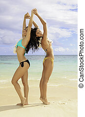two girls doing yoga at the beach