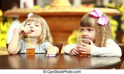 Two girls drinking juice and lookin