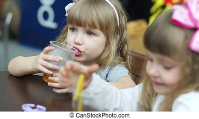 Two girls drinking juice at a cafe