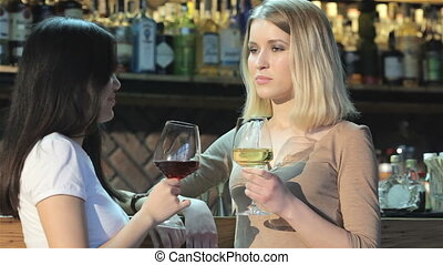 Two girls drinking wine at the bar