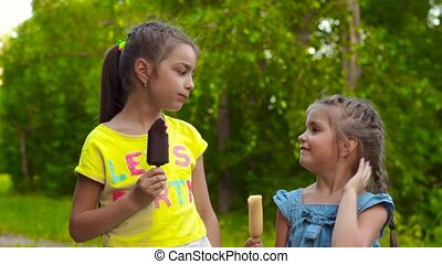 Two little girls in dress eating sweet delicious ice-cream popsicle in green summer park