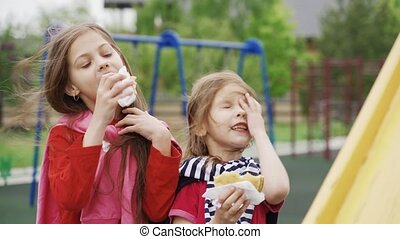 Two girls eating sandwiches outdoor on children playground. ...