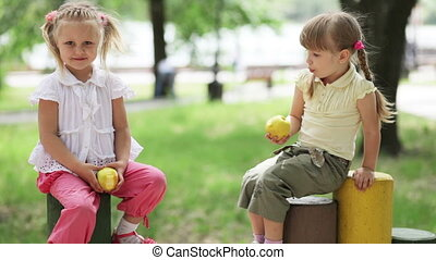 Two girls eating the apples in the