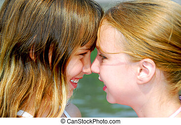 Two girls faces - Portrait of two young happy girls