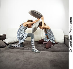 girls fighting with cushions on couch