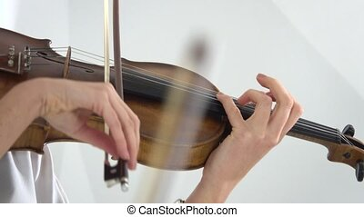 Two girls fingering the strings playing on a violins. Close up