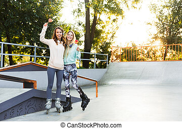 Two girls friends sisters on rollers in park outdoors holding sweeties candy.