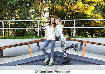 Two girls friends sisters on rollers in park outdoors.