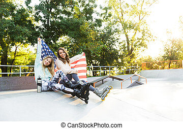 Two girls friends sisters on rollers sitting in park outdoors holding flag USA.
