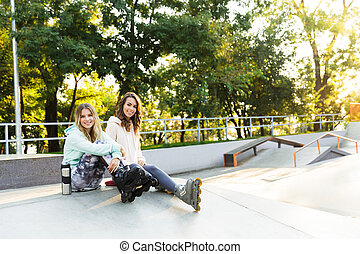 Two girls friends sisters on rollers sitting in park outdoors.