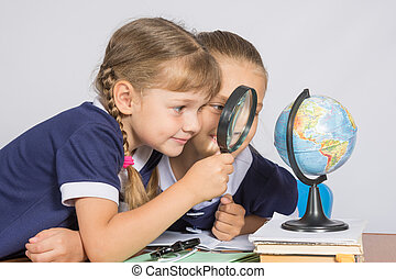 Two girls girlfriends looking at globe through a magnifying glass