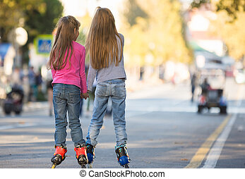 Two girls girlfriends rollerblading on the mall, rear view