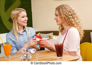 Two girls giving each other presents in cafe