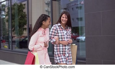 Two girls go after shopping holding shopping bags. slow motion