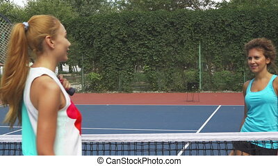 Two girls greeting on a tennis court