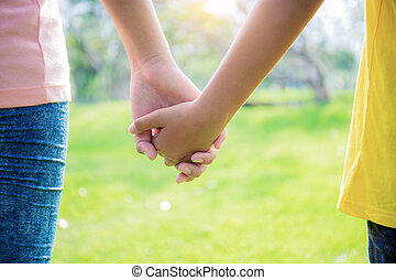 Two girls hand in park.