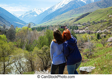 Two girls happily photographed against the backdrop of the mountains. Travelers take a selfie on the background of a beautiful mountain gorge. High snowy mountains and green trees in front of them.