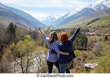 Two girls happily raise their hands up. Travelers on the background of a beautiful mountain gorge. High snowy mountains and green trees in front of them.