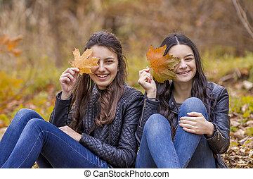Two girls having fun in autumn park