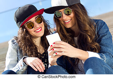 Two girls having fun with smartphones