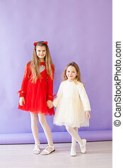 Two girls hold hands in red and white dresses