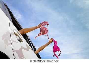 two girls holding bikini in the car